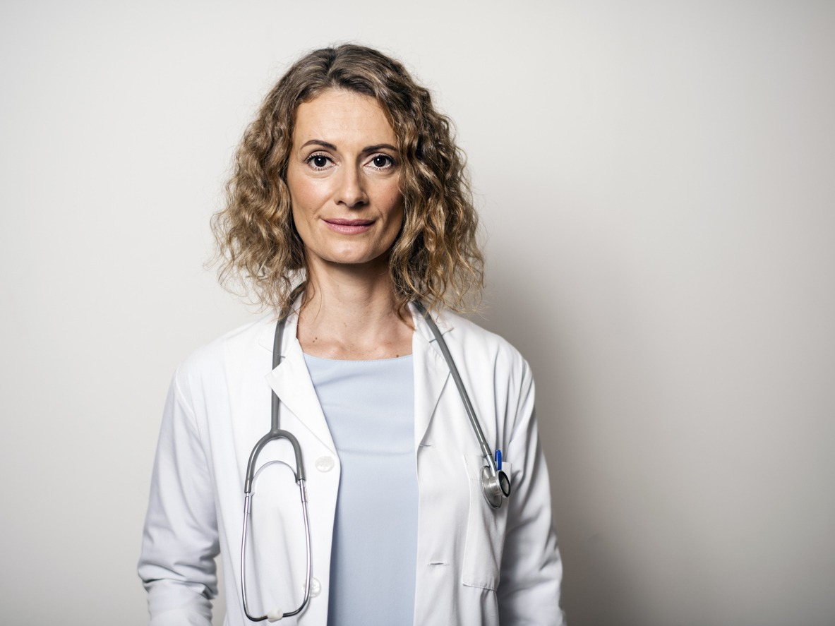 Portrait of female doctor against wall in hospital